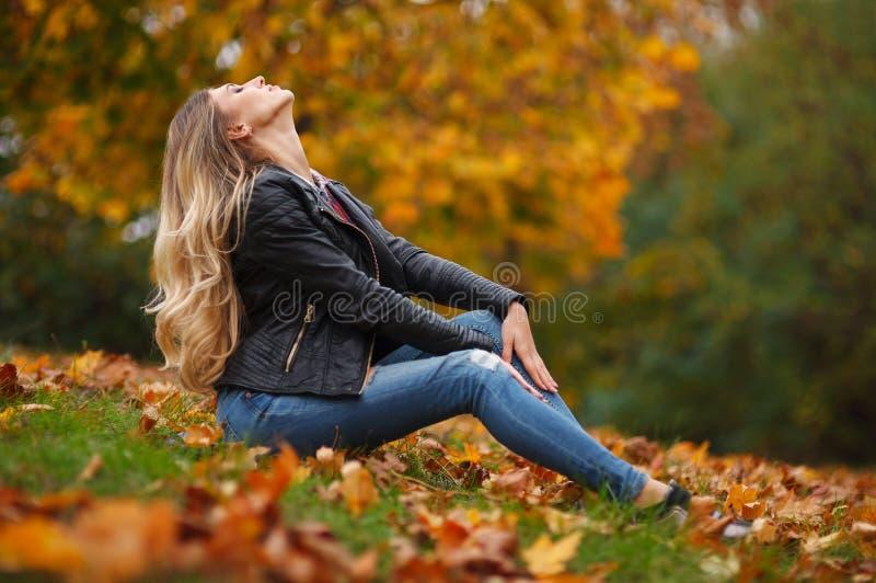 Portret piękna śliczna blondynki młoda kobieta w ładnej czarnej kurtce i modnych cajgach Pozowa? na z?otym jesieni natury tle zdjęcie royalty free