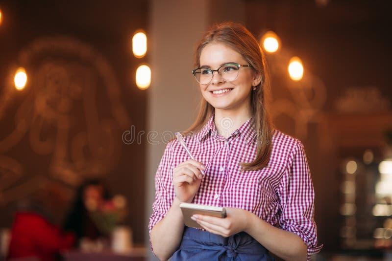 Portret piękna życzliwa kelnerka w szkłach z notepapers i pióro przygotowywający brać twój rozkaz zdjęcie stock