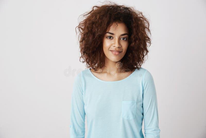 Portret piękna afrykańska dziewczyna ono uśmiecha się patrzejący kamerę Biały tło zdjęcie stock