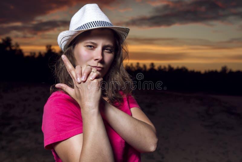 Portret piękna Amerykańska dziewczyna w kowbojskim kapeluszu składał jej ręki z pistoletem przeciw pięknemu niebu przy zmierzchem obrazy royalty free