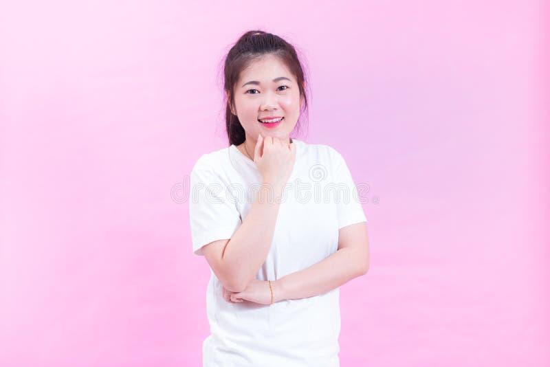 Portret Piękna Azjatycka kobieta myśleć o pytaniu z uśmiech odzieży białą koszulką na różowym tle obrazy stock