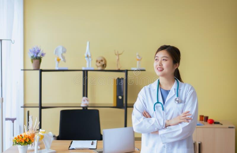 Portret piękna azjatykcia kobiety lekarki krzyża ręka i pozycja przy szpitala, Szczęśliwej i pozytywnej postawy główkowaniem, obraz stock