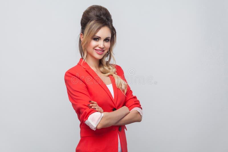 Portret piękna biznesowa dama z fryzurą i makeup w czerwieni mamy ochotę blezer, pozycję, falcowanie rękę i patrzeć kamerę, obraz royalty free