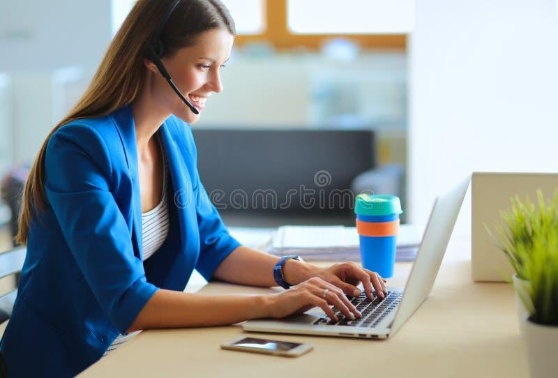 Portret piękna biznesowa kobieta pracuje przy jej biurkiem z słuchawki i laptopem obraz stock