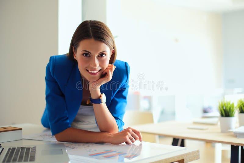Portret piękna biznesowa kobieta stoi blisko jej miejsca pracy zdjęcie royalty free