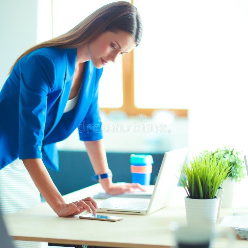 Portret piękna biznesowa kobieta stoi blisko jej miejsca pracy zdjęcia stock
