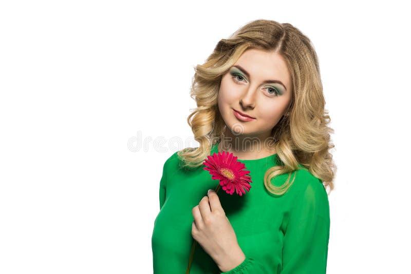 Portret piękna blondynki kobieta która jest przyglądająca kamera trzyma gerbera kwiatu dalej odizolowywa białego tło obraz stock