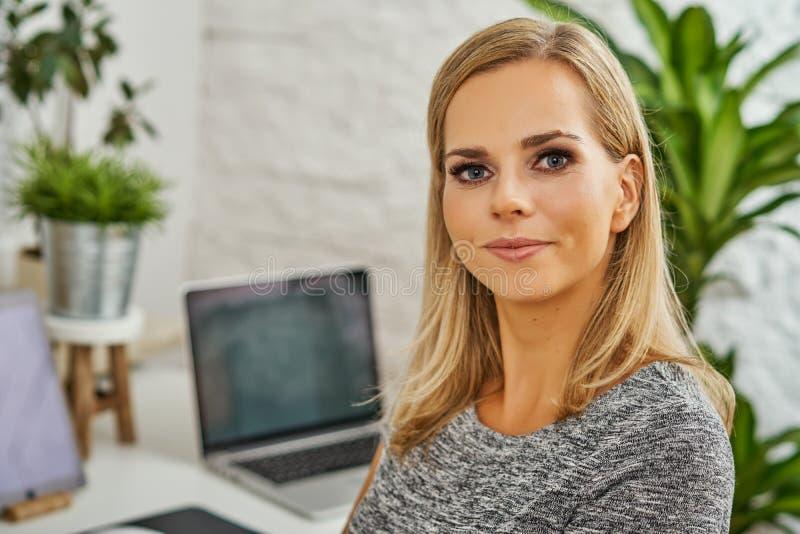 Portret piękna blondynki kobieta pracuje przy biurkiem w biurze obraz stock
