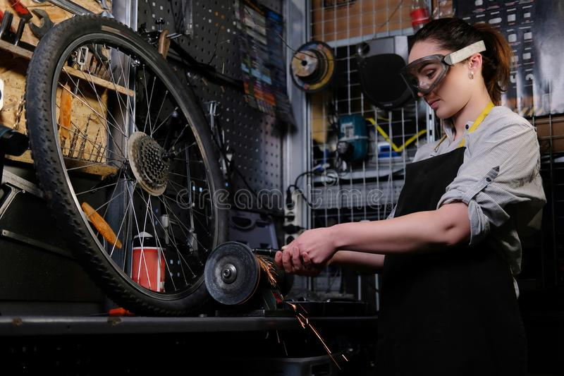Portret piękna brunetki kobieta jest ubranym pracujących ubrania fartuch i gogle pracuje na ostrzenie maszynie w a, zdjęcie stock