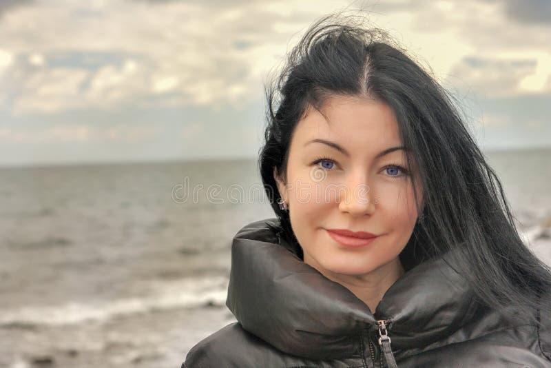 Portret piękna brunetki kobieta w zimy morzu obrazy royalty free