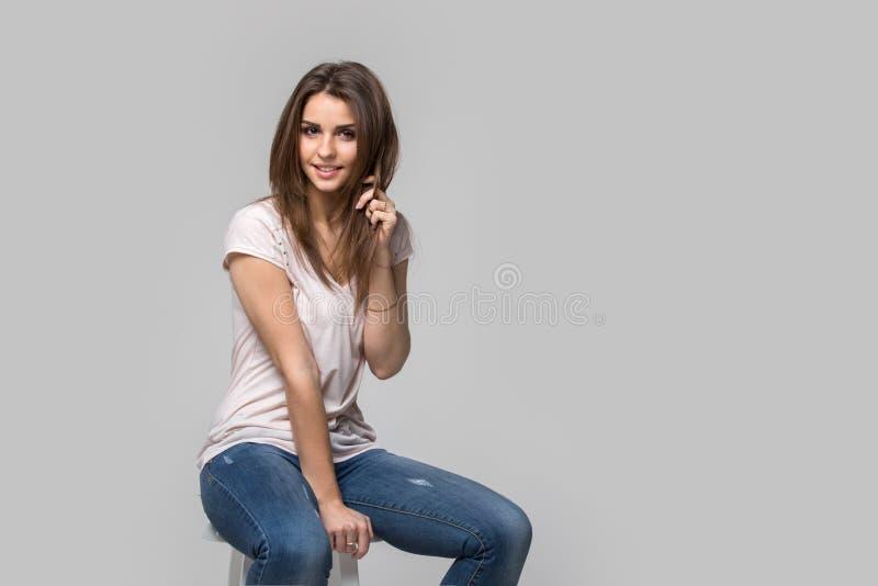 Portret piękna brunetki kobieta z naturalnym makijażem na popielatym tle, obraz stock