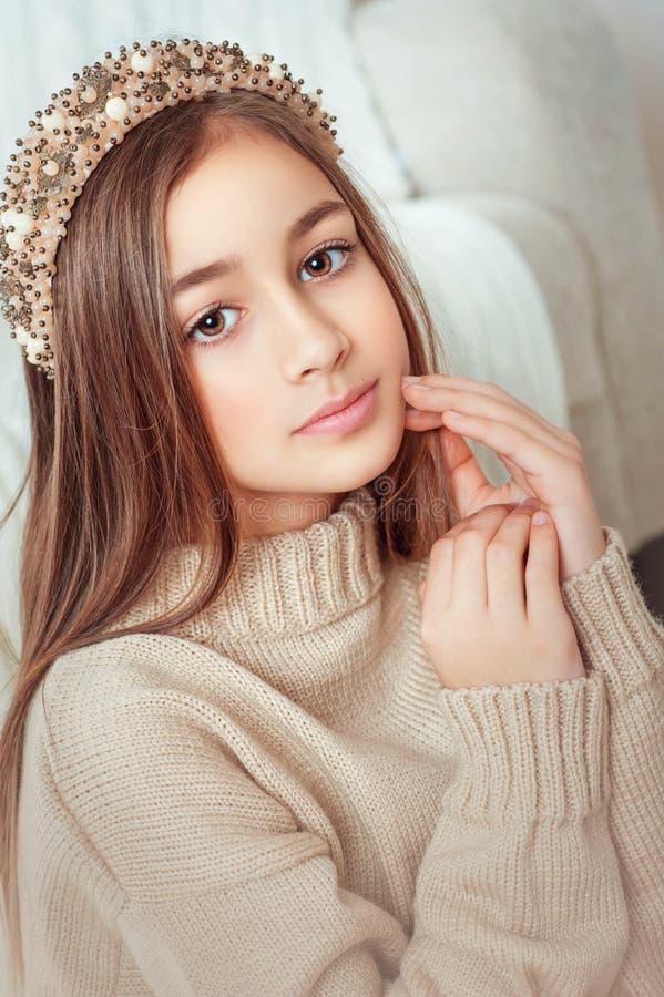Portret piękna czuła mała dziewczyna ubierał w pulowerze i pięknym akcesorium na głowie w domu fotografia stock