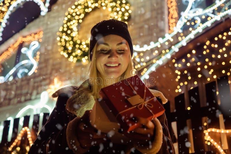 Portret piękna dziewczyna która otwiera magicznego Bożenarodzeniowego prezent wewnątrz zdjęcia royalty free