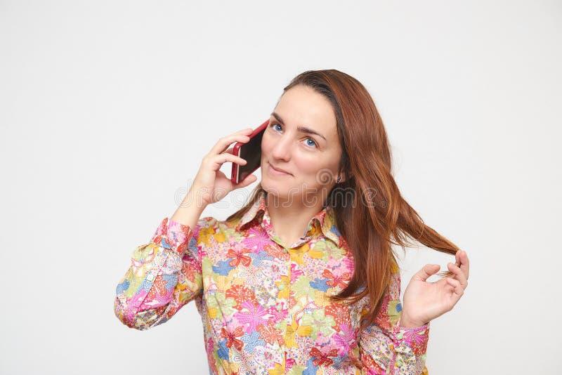 Portret piękna dziewczyna opowiada na telefonie bawić się z włosy w kolorowej koszula Na biały tle Brown włosiany kolor zdjęcia royalty free