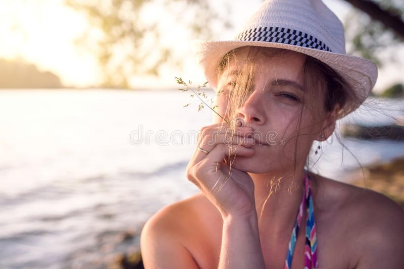 Portret piękna dziewczyna w kapeluszu z słomianym ostrzem trawa przeciw lata jeziornemu tłu przy zmierzchem na ciepłym wieczór zdjęcia stock
