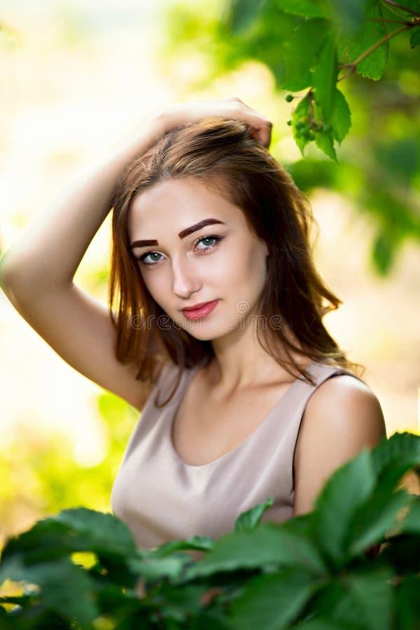 Portret piękna dziewczyna w lato ogródzie, młoda kobieta w zielonym ulistnieniu obrazy stock