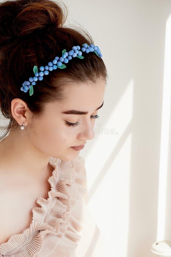 Portret piękna dziewczyna z ciemnego włosy i światła porcelany skórą Włosy w babeczce Włosiany akcesoryjny handmade fotografia royalty free