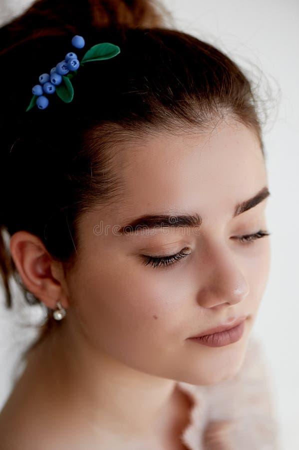 Portret piękna dziewczyna z ciemnego włosy i światła porcelany skórą Włosy w babeczce Włosiany akcesoryjny handmade obraz stock