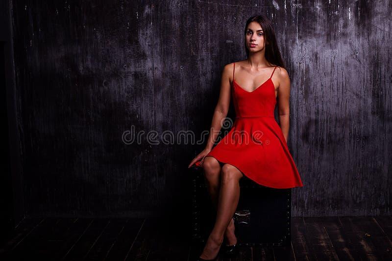 Portret piękna dziewczyna z makeup i długim brunetka włosy jest ubranym czerwieni suknię obraz royalty free