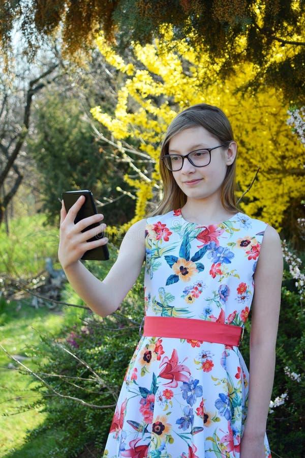 Portret piękna dziewczyna z szkłami i brązu włosy robi selfie na mądrze telefonie Młody uśmiechnięty teneeger w zielonym wiosna p obrazy stock