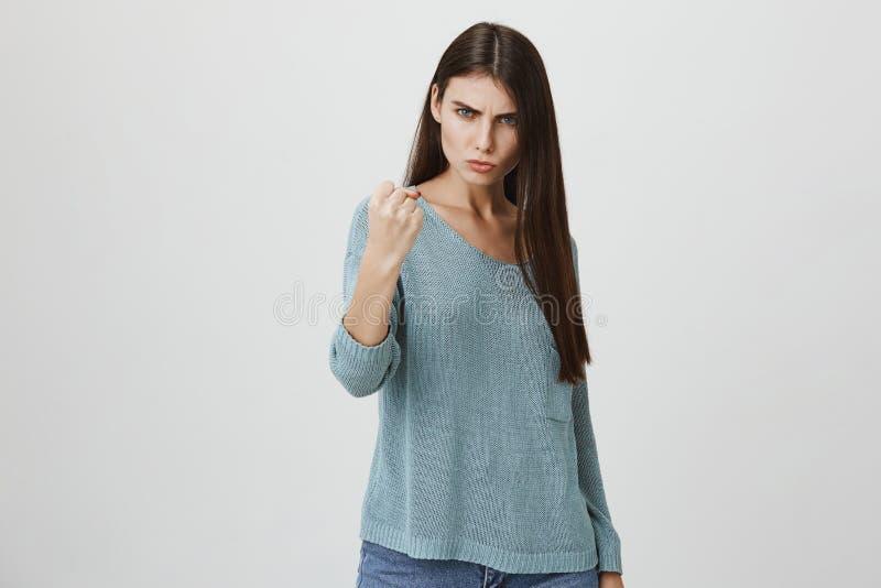 Portret piękna europejska kobieta pokazuje agresję z językiem ciała i nastroszoną pięścią, zagraża someone podczas gdy obraz royalty free