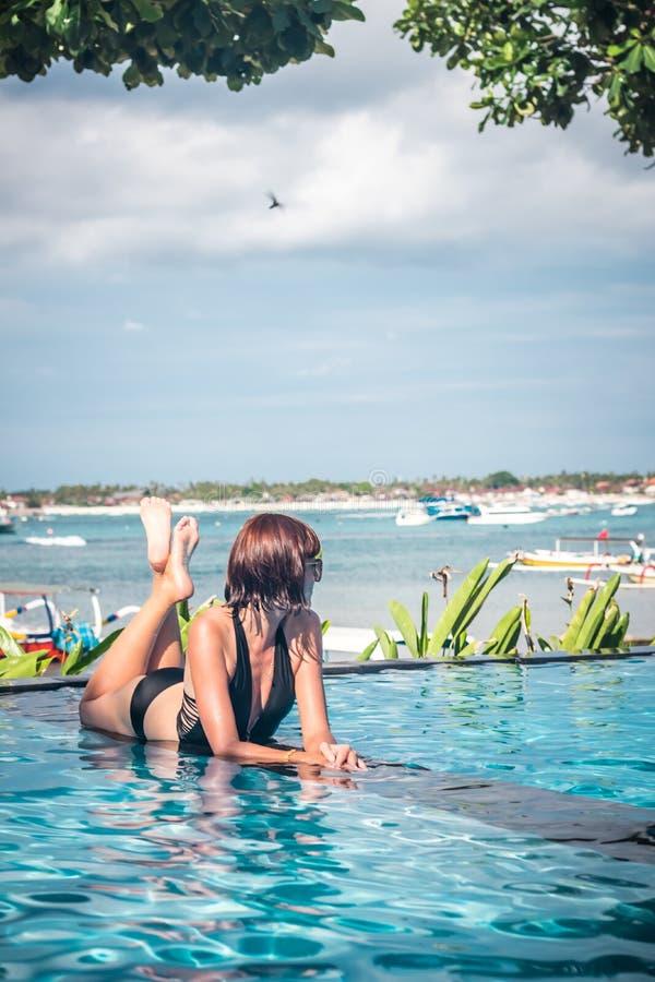 Portret piękna garbnikująca kobieta relaksuje w pływackiego basenu zdroju w czarnym swimwear Gorący letni dzień i jaskrawy pogodn obrazy stock