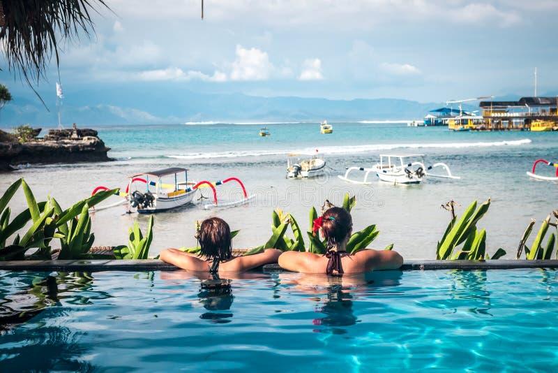 Portret piękna garbnikująca kobieta relaksuje w pływackiego basenu zdroju w czarnym swimwear Gorący letni dzień i jaskrawy pogodn zdjęcie stock
