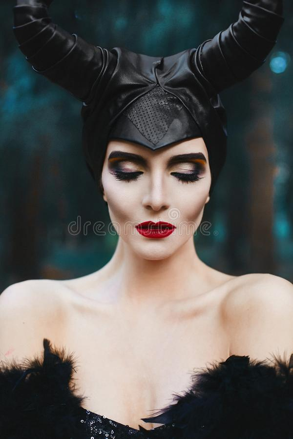 Portret piękna i modna brunetki schudnięcia modela dziewczyna z jaskrawym makeup i czerwonymi wargami przy tajemniczym lasem, - zdjęcie royalty free