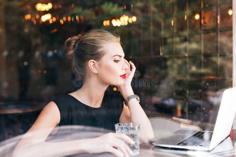Portret piękna kobieta przez szklanego okno obsiadania w bufecie Czerwone wargi, trzyma szkło w ręce, patrzeje zdjęcie royalty free