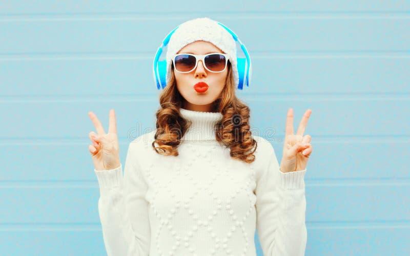 Portret piękna kobieta słucha muzyka w hełmofonach w bielu fotografia royalty free