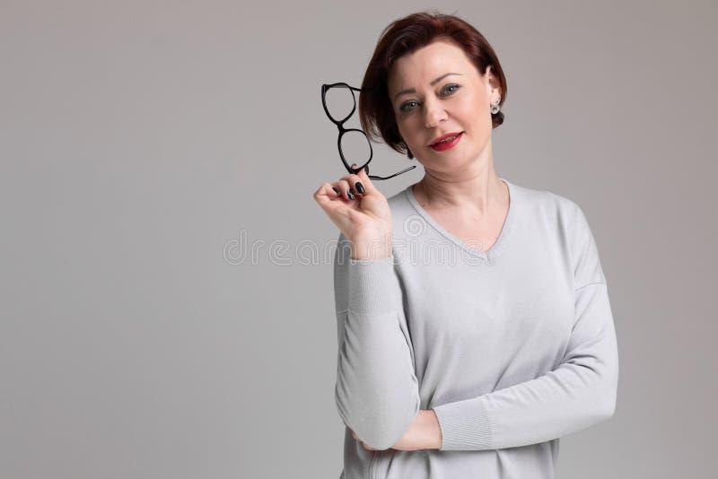 Portret piękna kobieta w świetle odziewa z szkłami w ręce na lekkim tle zdjęcia royalty free