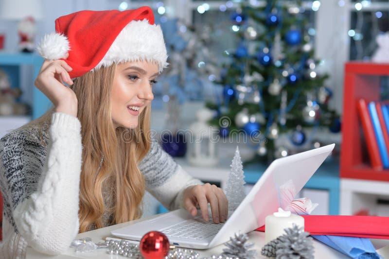 Portret piękna kobieta w Santa kapeluszowym używa laptopie zdjęcie royalty free