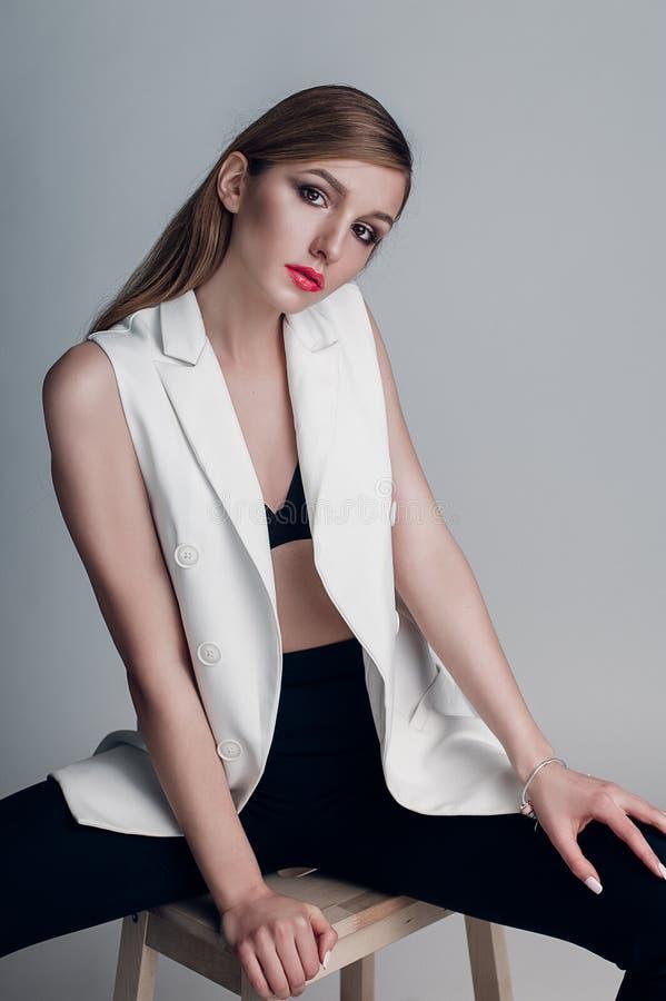 Portret piękna kobieta z kreatywnie makijażu koralowymi wargami w białej kurtce gładzi włosy i moczy fotografia royalty free