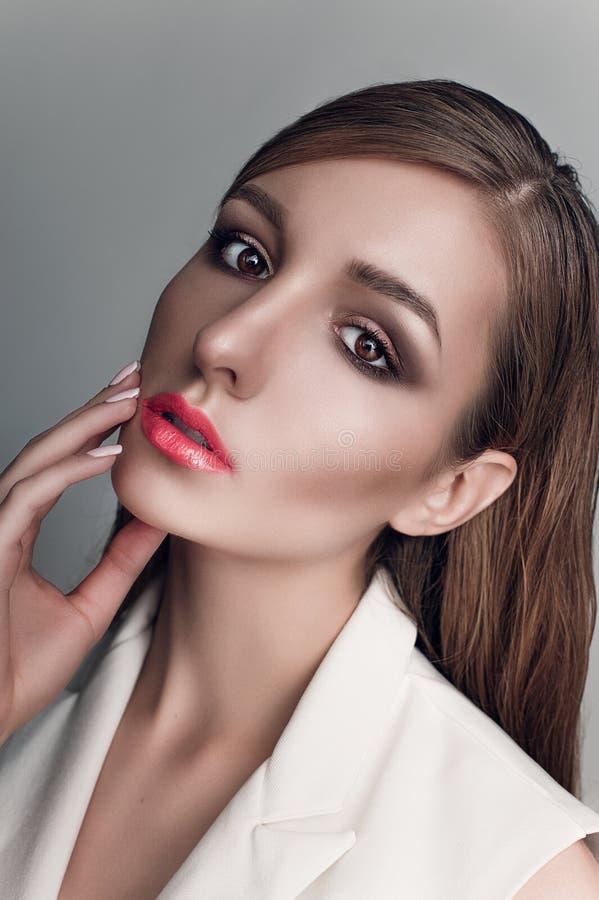 Portret piękna kobieta z kreatywnie makijażu koralowymi wargami w białej kurtce gładzi włosy i moczy zdjęcie stock