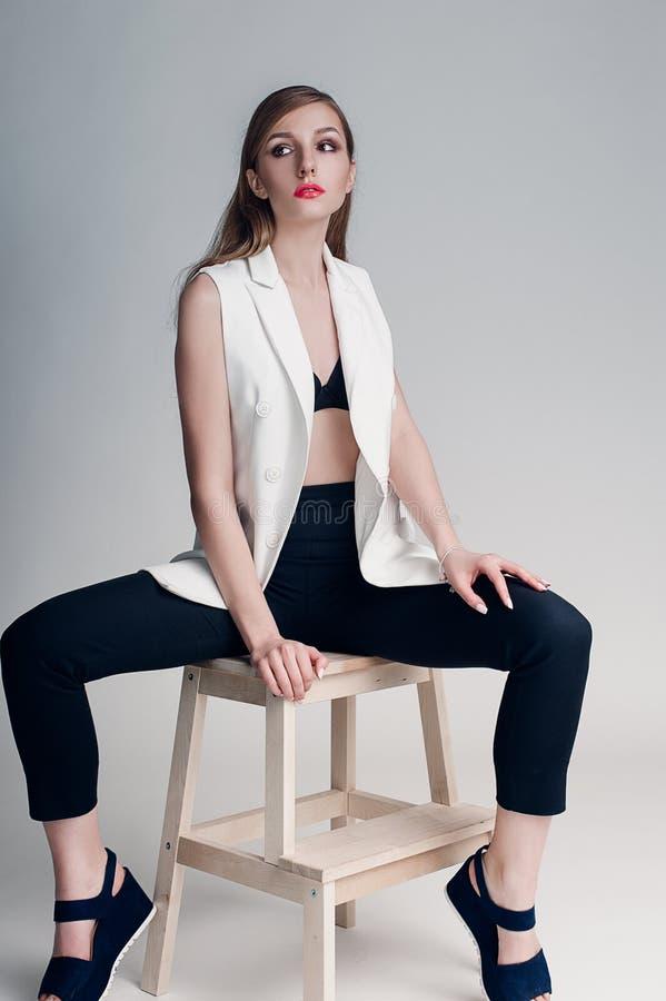 Portret piękna kobieta z kreatywnie makijażu koralowymi wargami w białej kurtce gładzi włosy i moczy zdjęcie royalty free
