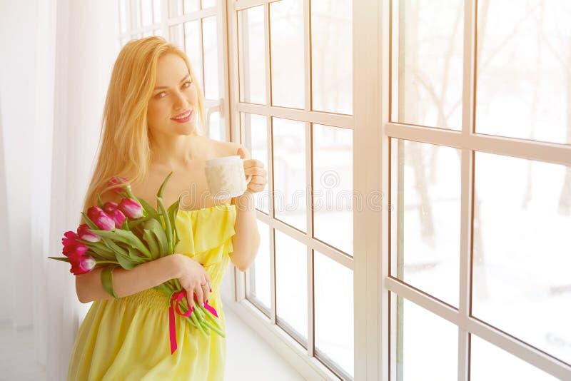 Portret piękna kobieta z tulipanową bukieta i filiżanki herbatą sunlight obrazy stock