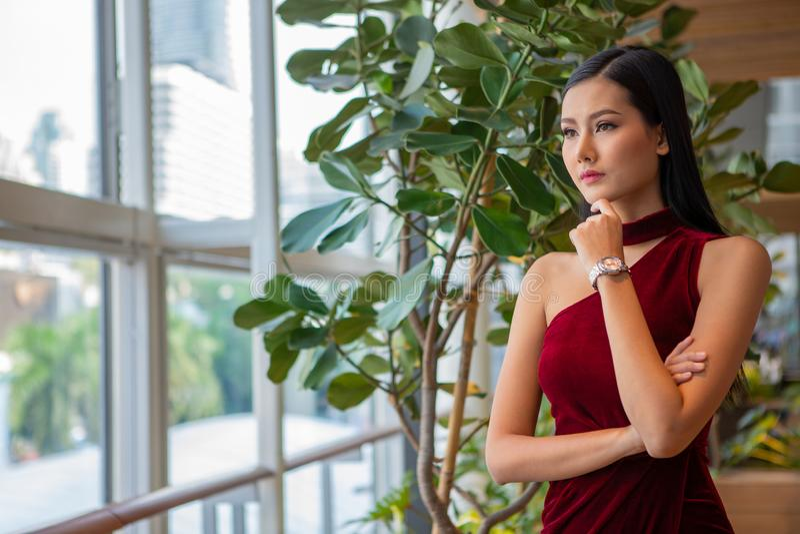 portret Piękna młoda azjatykcia kobieta w czerwieni sukni pozycji i przyglądający za okno elegancki dama modela główkowanie i cze fotografia stock