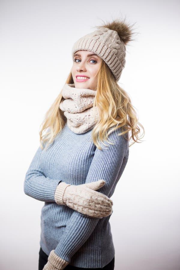 Portret piękna młoda blondynki kobieta jest ubranym ciepłego trykotowego pulower, kapelusz, szalika i mitynki na białym tle, Szcz obrazy royalty free