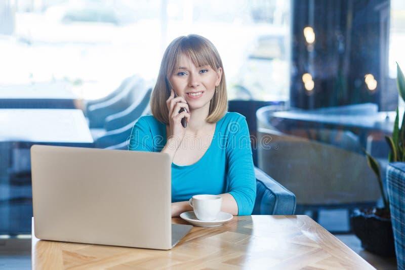 Portret piękna młoda blondynki kobieta w błękitnym koszulki obsiadaniu i działanie w kawiarni z laptopem mienie telefon komórkowy zdjęcia stock