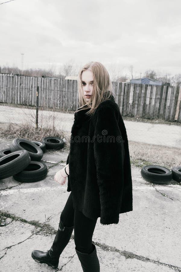 Portret piękna młoda blondynki kobieta w czarnej kurtce na ulicie, chmurny obrazy royalty free