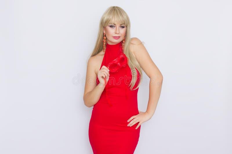 Portret piękna młoda blondynki kobieta z długie włosy w czerwonej wieczór sukni Dziewczyna stawia dalej czerwoną karnawał maskę n fotografia stock