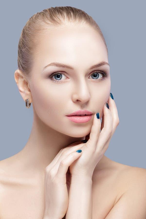 Portret piękna młoda blondynki kobieta z niebieskimi oczami na popielatym tle stawia czoło jej wzruszającej kobiety zdjęcie stock