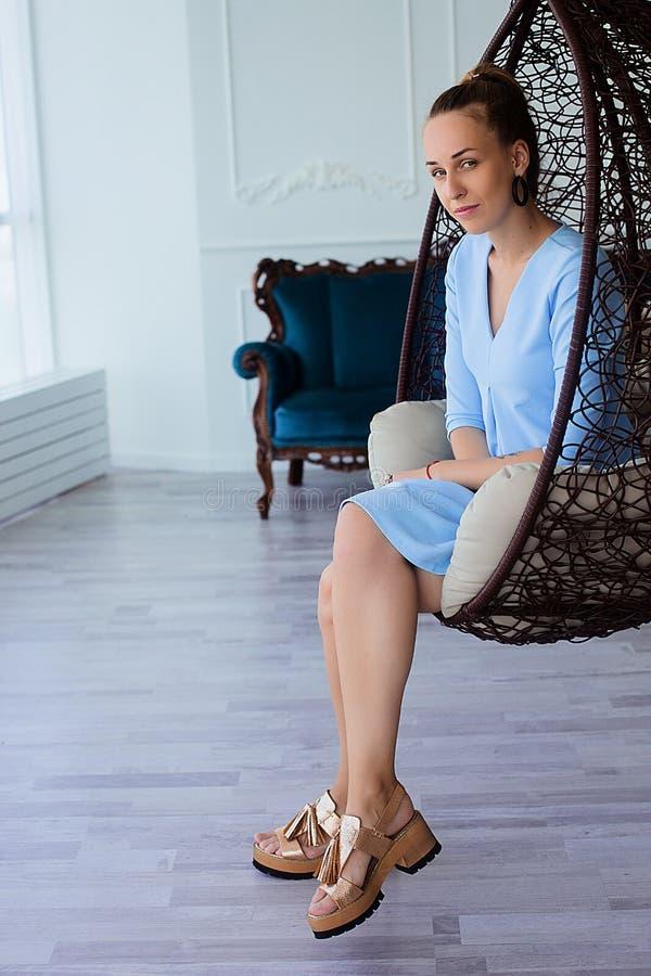 Portret piękna młoda brunetki kobieta w błękit sukni z uzupełniał i ponytail, siedzi w wielkim krześle fotografia royalty free