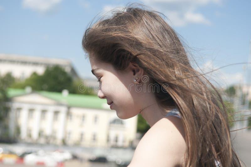 Portret piękna młoda dziewczyna z podmuchowym włosy w wiatrze w miasta niebieskiego nieba tle zdjęcia stock