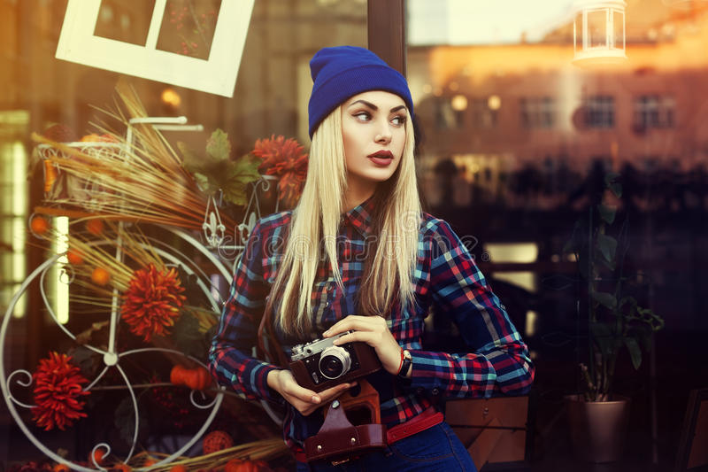 Portret piękna młoda figlarnie modniś kobieta z starą retro kamerą na boku patrzejący wzorcowy tła piękna miasta styl życia miast zdjęcie stock