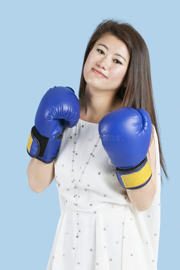 Portret piękna młoda kobieta jest ubranym bokserskie rękawiczki nad błękitnym tłem zdjęcia royalty free