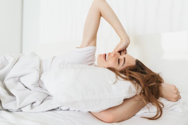 Portret piękna młoda kobieta kłaść w łóżku fotografia royalty free