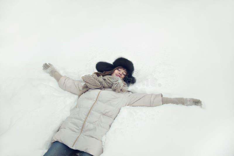Portret piękna młoda kobieta kłaść w dół na śnieżnej anioł postaci zdjęcia royalty free