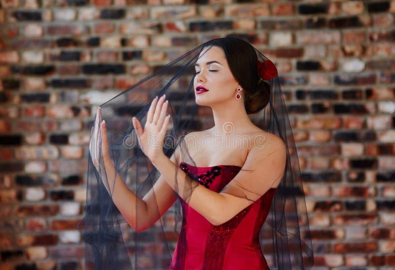 Portret piękna młoda kobieta w czerwonej sukni pod czarną przesłoną zdjęcie royalty free