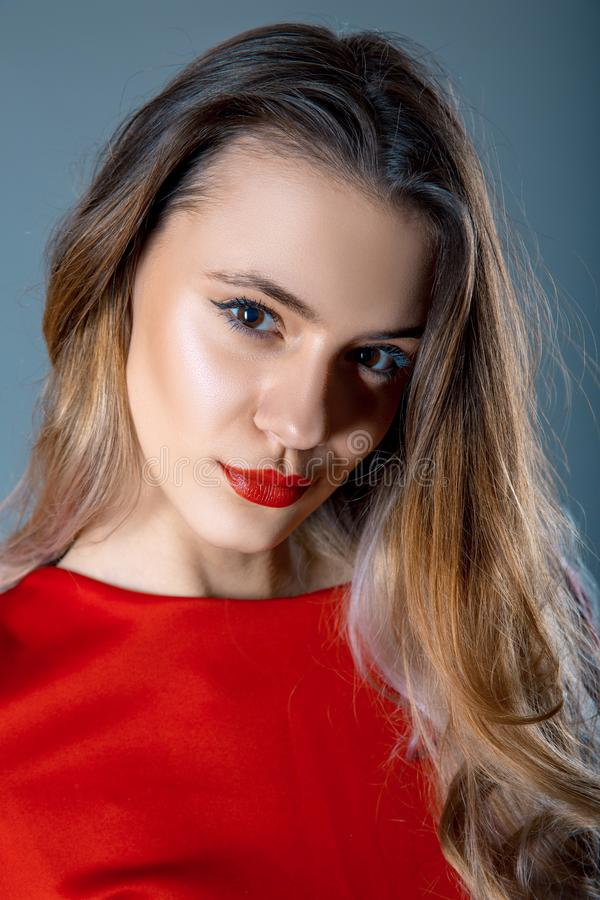 Portret piękna młoda kobieta z czerwonymi wargami i czerwień ubieramy na błękitnych szarość tle fotografia stock